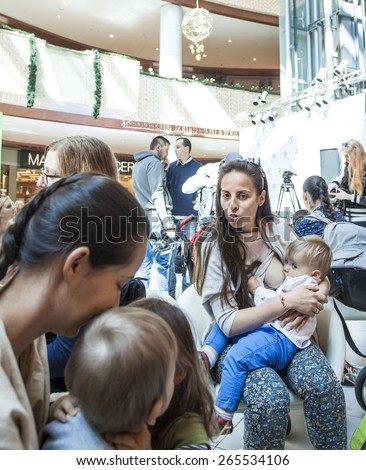 Sofia, Bulgaria - March 30, 2015: Mothers breastfeed their children in urban mall in protest. Flatter woman was kicked by the guards of the mall, because feeding her baby from her breast in public. - stock photo