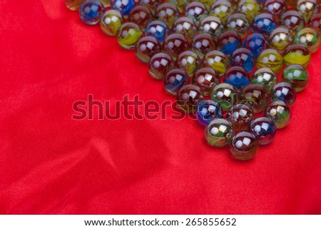 Soft abstract image of colourful marbles on red background with copy space. - stock photo