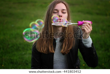 Soft and blur conception. Young beautiful girl blowing colorful bubbles outdoors