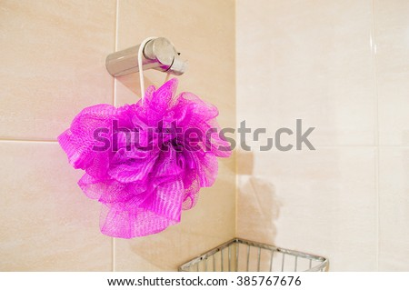 Soft bath puff or sponge hanging on bathroom background with copy space. - stock photo