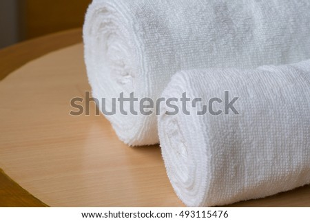 soft bath towel rolled up on wooden table