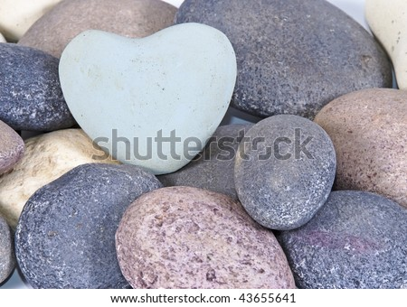 Soft blue heart shaped stone on multi-colored stones - can be used for Valentine's day - stock photo