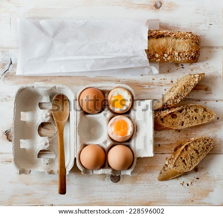 Soft boiled eggs in a crate cardboard box and wholemeal bread on a rustic table. - stock photo