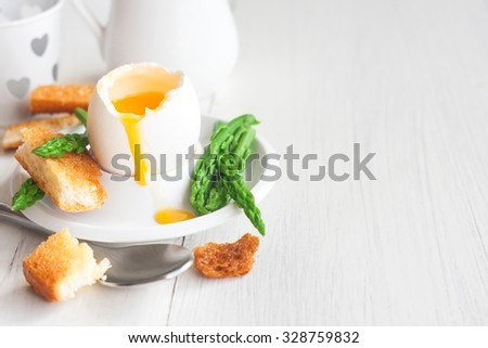 Soft boiled eggs with asparagus and toast soldiers. Copy space background. - stock photo