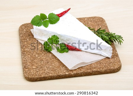 Soft brie cheese with rosemary, thyme on the wood background - stock photo