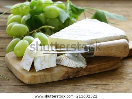 Soft brie cheese with sweet grapes on a wooden board - stock photo