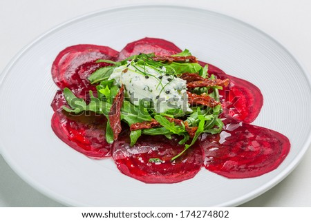 Soft cheese with sliced beetroot, sun dried tomato and rocket leaf salad garnished with sprouts - stock photo