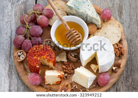 soft cheeses and snacks on a wooden background, close-up, top view, horizontal