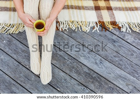 Soft cozy photo of Girl sitting on checkered plaidwith cup of tea in hands, top view point - stock photo