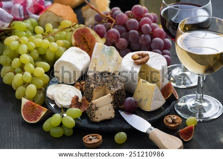 soft delicacy cheeses and snacks for wine on a dark background, close-up - stock photo