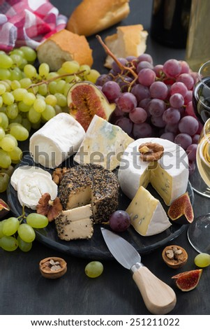 soft delicacy cheeses and snacks for wine on a dark background, vertical, top view - stock photo