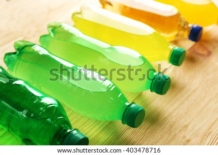 Soft drinks bottles on the wooden table, close up - stock photo