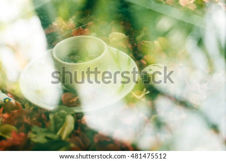 Soft focus and blurry background of white coffee cup under the glass table in coffee shop.Vintage style.