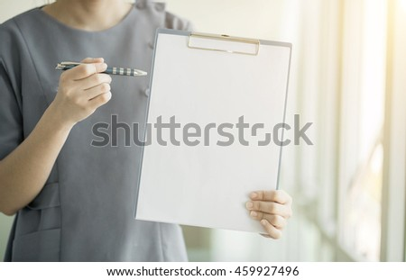 Soft focus Asian medical  female doctor or nurse  holding patient medical chart in hospital (Color tone added) with copyspace and blurred background. - stock photo