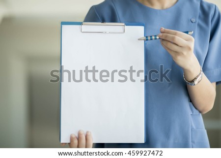 Soft focus Asian medical  female doctor or nurse  holding patient medical chart in hospital with copyspace and blurred background. - stock photo