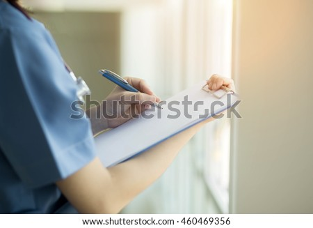 Soft focus Asian medical female doctor or nurse writting a patient medical chart and  in hospital with copyspace and blurred background. - stock photo