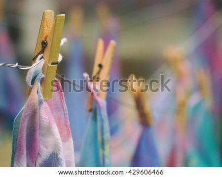 Soft focus clothespin hanging with tie dye on blurred background, hand made tie dye background - stock photo