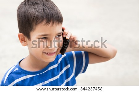 Soft focus image of happy little boy talking on the phone with his parents on light background with copy-space. Shallow DOF