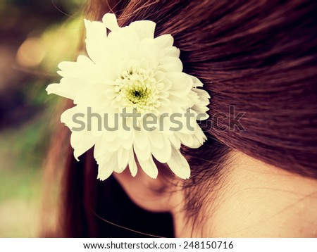 Soft focus of beautiful fresh white flower behind woman's ear in vintage style. - stock photo
