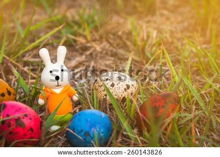 soft focus of easter decorate with rabbit toy and easter eggs on grass field background. vintage color tone.  - stock photo