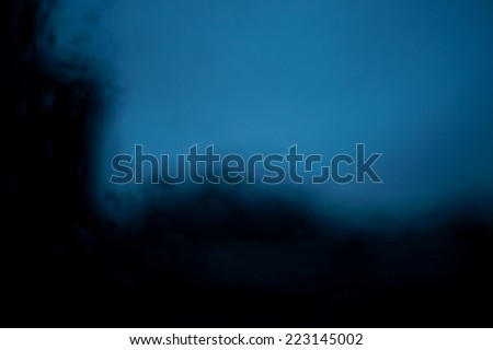 Soft focus of raindrops on a window with a view on a city buildings at dawn - stock photo