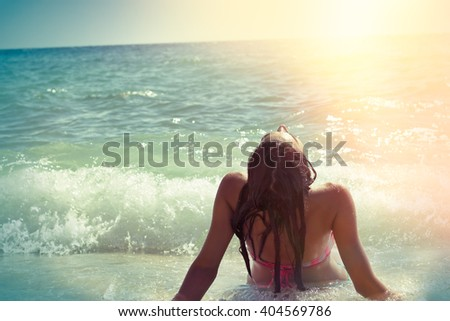 Soft focus on young girl - Young girl enjoying the sun and in waves of the sea on sandy beach - stock photo