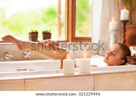 Soft focus photo of gentle young woman lying down in bath tub with foam and candle, enjoying spa procedure in the luxury resort - stock photo