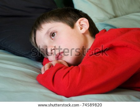 soft focus portrait of a young boy laying on his bed looking sad and lonely