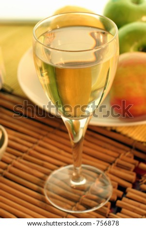 Soft focus shot of a glass of cider or fruit wine. - stock photo