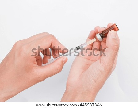 Soft focus Syringe with vial on hands of a nurse,doctor administer the injection isolated on white background. - stock photo
