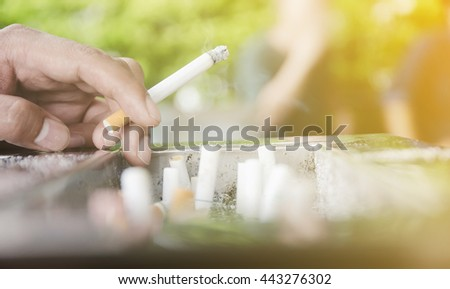 Soft focus technique. Close up of man smoking a cigarette with sunlight at the outdoor park. Man hand holding a cigarette on people background. - stock photo