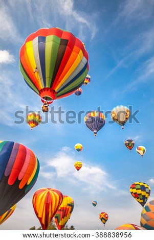 soft-focused hot-air balloons with blue sky and clouds background - stock photo