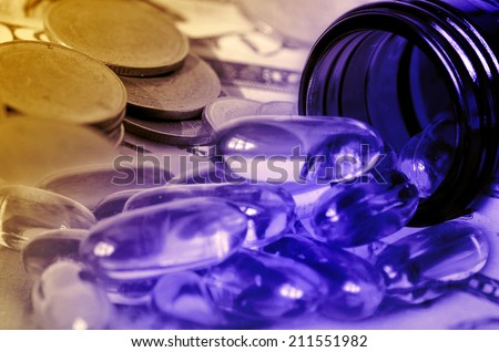 Soft gelatin dietary supplement oil capsule and money in drug expense concept. - stock photo