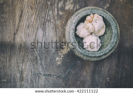 Soft Image of the garlic and stone mortar on old wooden. The Selective focus with shallow depth of field. image with classic tone ,vintage effect and some noise added. - stock photo