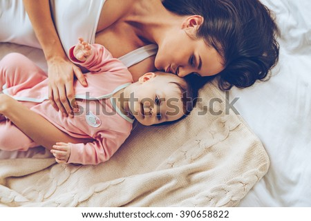 Soft kiss from mommy. Top view of cheerful beautiful young woman lying in bed with her baby girl and kissing her - stock photo