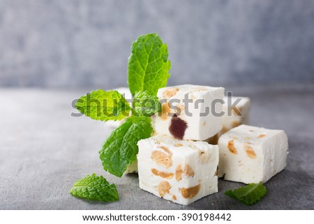 Soft nougat blocks with peanuts and fruit with fresh mint leaves on gray background with copy space. Holiday concept. - stock photo
