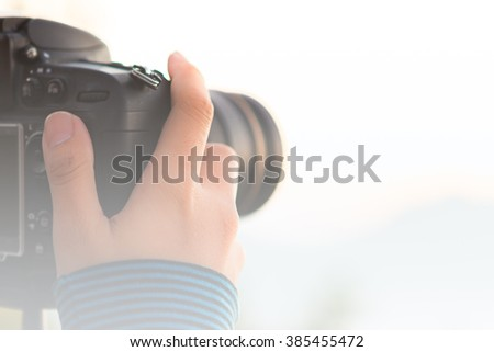 Soft of Focus : Photographer's hand on  DSLR camera focus at sunrise lanscape sceen - stock photo