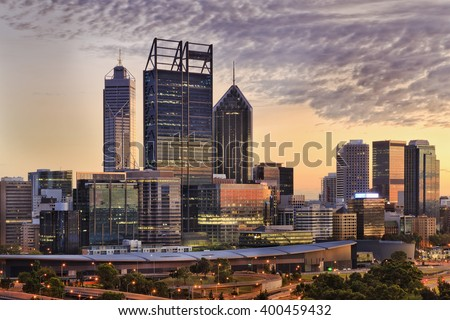 Soft peach sun light at sunrise lit the Perth city CBD skyscrapers and business towers as seen from Kings park. - stock photo