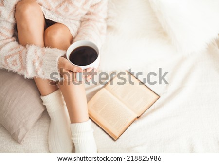 Soft photo of woman on the bed with old book and cup of coffee in hands, top view point. Cozy, comfy, soft - stock photo