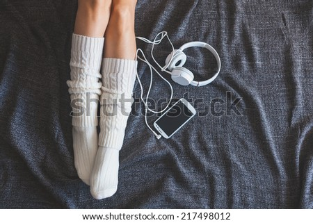 Soft photo of woman on the bed with smartphone and headphones, top view point - stock photo