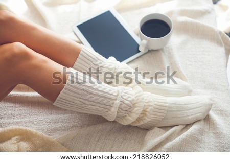 Soft photo of woman on the bed with tablet and cup of coffee, top view point. Cozy, comfy, soft - stock photo