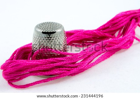 soft pink cotton thread and a thimble - stock photo
