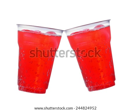 Soft plastic cups with red drink on a white background.