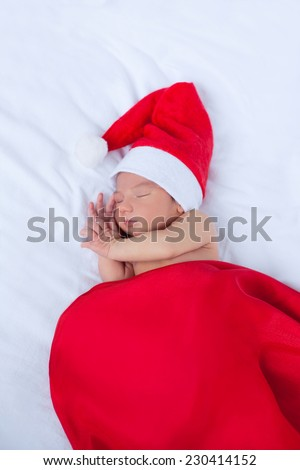 Soft portrait of newborn baby boy kid in red santa claus hat, sleeping on white background. Focus on close eye, cheek and hand. Merry christmas and happy new year greeting card. - stock photo
