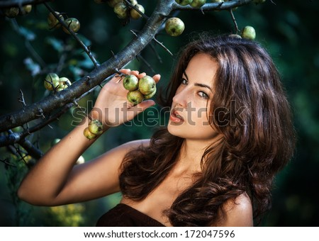 Soft portrait of young woman with wild apples - stock photo