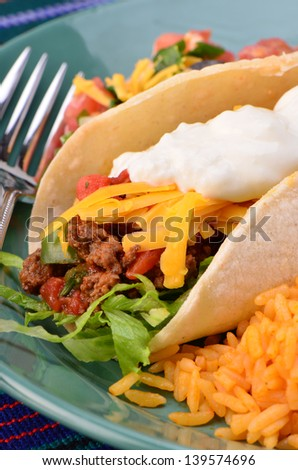 Soft tortilla with spicy ground beef, salsa , sour cream and cheese with Mexican rice - stock photo