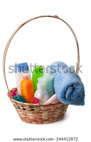 soft towel, soap, shampoo, cream, shower gel arranged in a basket - stock photo