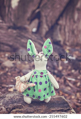 Soft toy - bunny sitting on an old tree. toned photo - stock photo