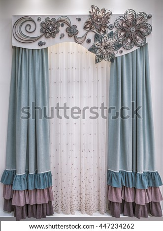 Soft velor curtains with colored frills, a light tulle and a stiff pelmet with lace applique. - stock photo