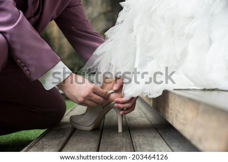 soft vintage tone image of groom assisting bride putting on her shoes - stock photo
